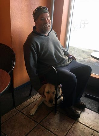 Buck working as a service dog-in-training at a restaurant