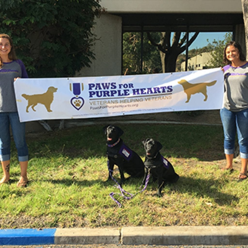 PPH Instructors Selah Marting and Kristen La Torre standing with two PPH pups in front of new facility