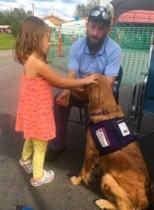 Veteran, Ken Richardson, volunteers for PPH with Sophie, service dog-in-training at the Tanana Valley State Fair.