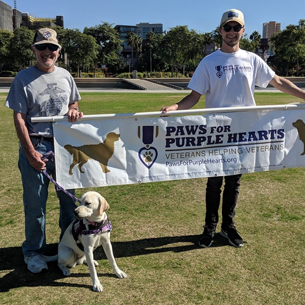 Volunteer Trainer, Michael (left) and our Advancement Associate, Ketcher (right) stand with Jules for the Parade. PPH SD Veterans Parade