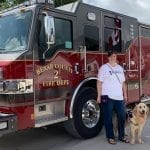 Noah and his handler Eric pose in front of a firetruck while waiting for the Perry Home dedication ceremony to begin